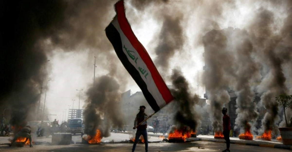 A protester holds an Iraqi flag amid a cloud of smoke from burning tires during ongoing anti-government protests in Najaf, Iraq November 26, 2019. (Reuters Photo)