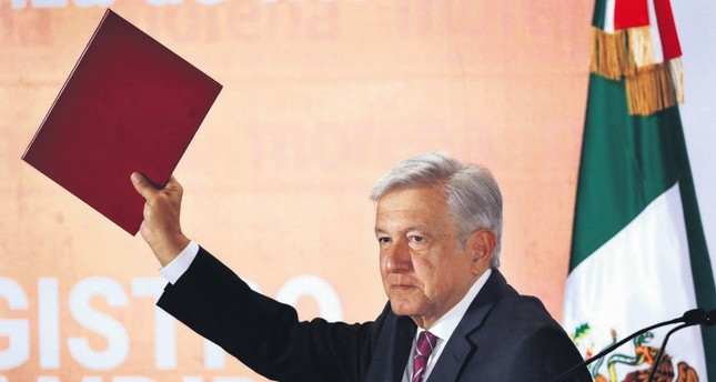 Mexico's President-elect Andres Manuel Lopez Obrador, more widely known as Amlo, holds up his candidacy application for the July 2018 elections.
