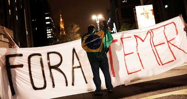 A demonstrator draped with a Brazilian Flag is pictured in front a banner reading  Temer out  during a protest against Brazil's President Michel Temer in Sao Paulo, Brazil, May 17, 2017. Reuters Photo