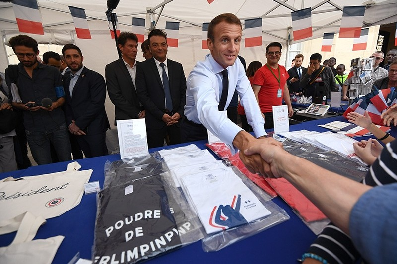 French President Emmanuel Macron shakes hands with a visitor next to items for sale at the Elysee Palace in Paris, Sept. 15, 2018. (EPA Photo)