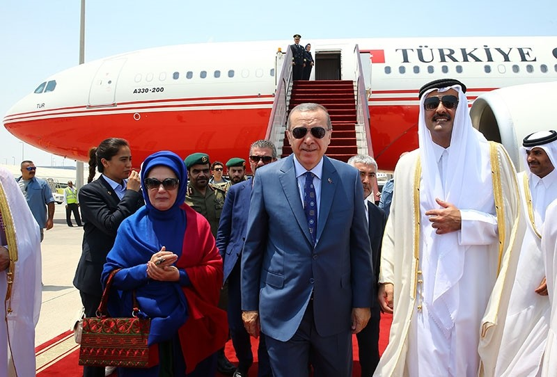 This handout photo taken and released by the  Presidential Press Service on July 24, 2017 shows President Recep Tayyip Erdou011fan (C) and his wife Emine Erdou011fan (L) being welcomed by Emir of Qatar Sheikh Tamim bin Hamad Al Thani (R) at Doha
