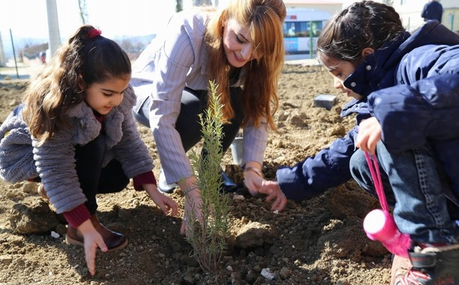 A woman helps two children plant a tree in Diyarbakır, Feb. 19, 2018. Turkey regularly holds afforestation drives to increase the number of trees.