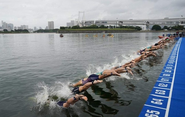 Athletes dive into the water during a triathlon test event at Odaiba Marine Park, a venue for marathon swimming and triathlon at the Tokyo 2020 Olympics, in Tokyo, Aug. 15, 2019. (AP Photo)