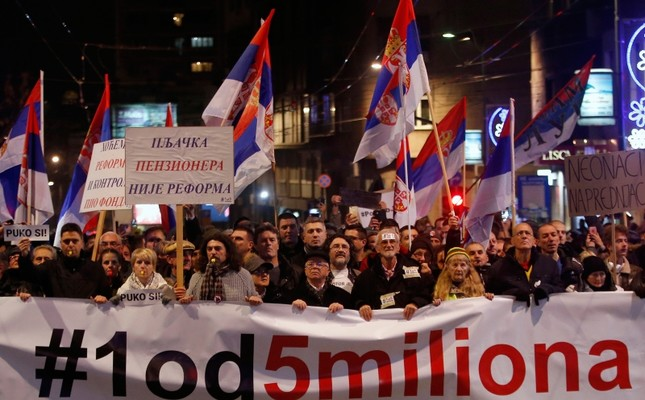 People hold a banner that reads: '#1out of 5 million' during a protest against President Aleksandar Vucic in Belgrade, Serbia, Saturday, Dec. 29, 2018. (AP Photo)