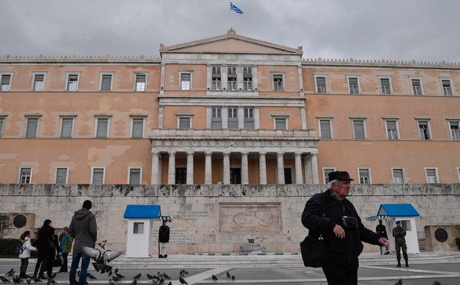 People walk in front of the Greek Parliament, central Athens, Feb. 8, 2019.