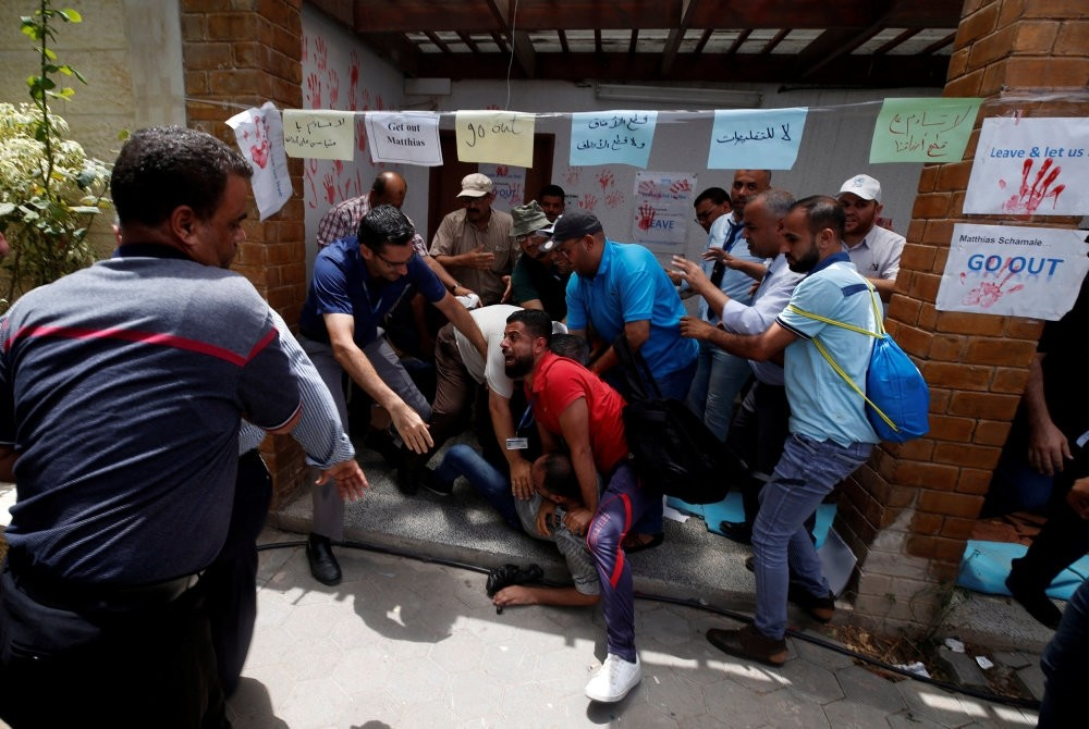 People prevent a Palestinian UNRWA employee from setting himself on fire, Gaza City, July 25.