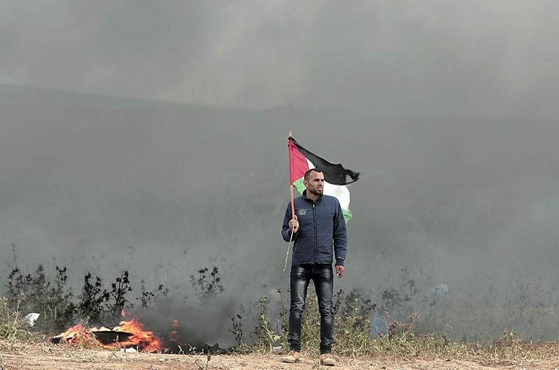 A Palestinian protester waves a national flag next to burning tires during clashes with Israeli troops along Gaza's border with Israel, east of Beit Lahiya, Gaza Strip, Tuesday, April 3, 2018. (AP Photo)