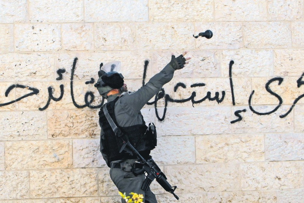 An Israeli soldier throws a teargas canister toward Palestinian protesters during clashes at the main entrance of the occupied West Bank town of Bethlehem, Dec. 12.
