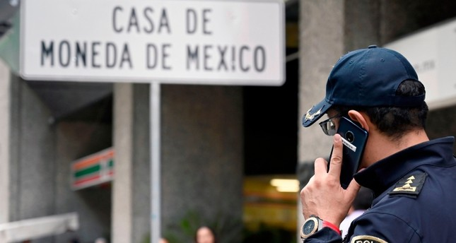 A policeman speaks on his mobile phone outside Mexico's Casa de Moneda, in Mexico City on August 6, 2019, which was robbed earlier today and the assailants took a swag of approximately two and a half million dollars in gold coins. (AFP Photo)