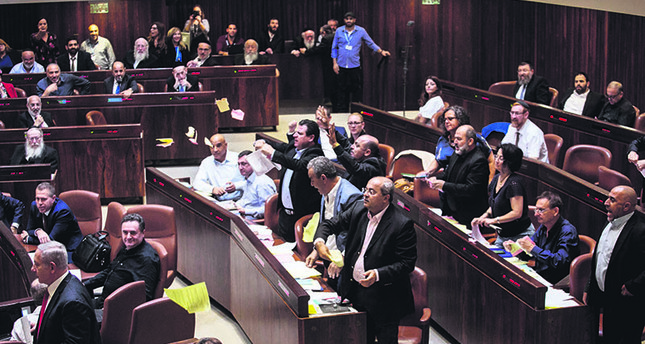 Arab lawmakers stand up in protest during a Knesset session against the parliament's approving a controversial bill to define Israel as the nation-state of the Jewish people, July 18, 2018. (AP Photo)