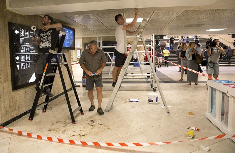 An investigator takes a photo and painters repair an area inside a cordon where an explosive device went off inside Central Station in Brussels on Wednesday, June 21, 2017. (AP Photo)