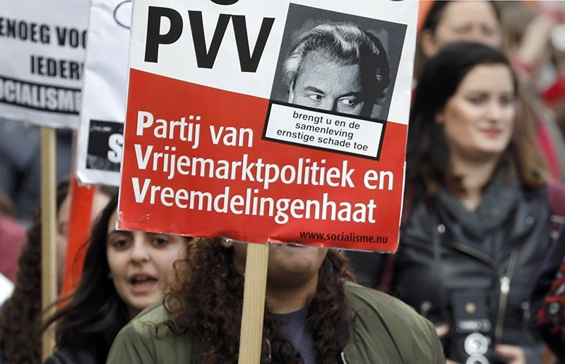 A demonstrator carries a sign reading ,PVV - The party of free market policy and xenophobia, , during a march in Amsterdam, Netherlands, March 11, 2017. (Reuters Photo)
