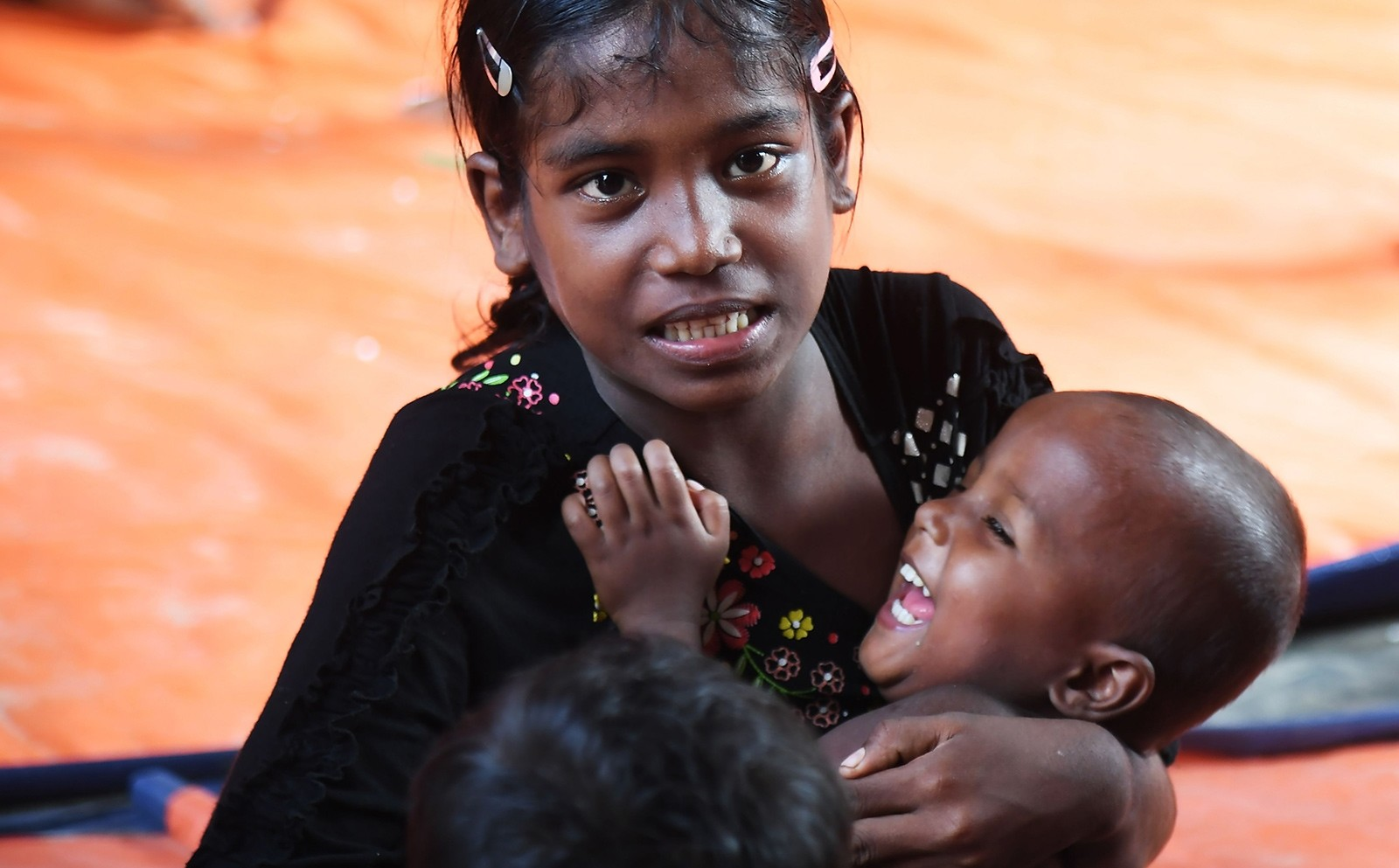This picture taken November 4, 2017 shows ten-year-old Rohingya refugee Tahera Begum playing with her sister as she attends an informal school at the Balukhali refugee camp in Bangladesh's Ukhia district (AFP Photo)
