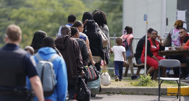 A group of asylum seekers wait to be processed after being escorted from their tent encampment to the Canada Border Services in Lacolle, Quebec, Canada August 11, 2017. (Reuters Photo)