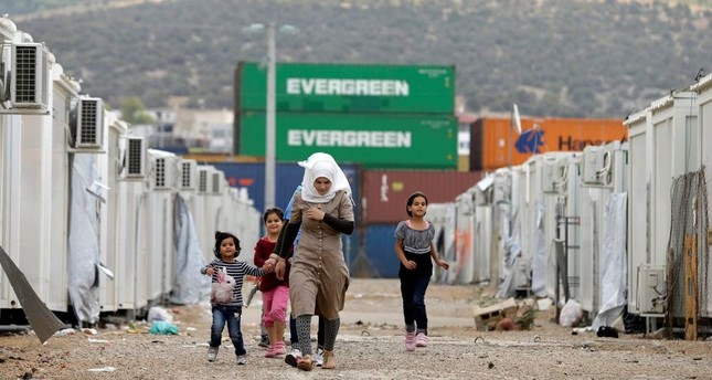 People walk at a refugee camp which houses about 3,200 refugees, in the western Athens' suburb of Skaramagas, Greece.