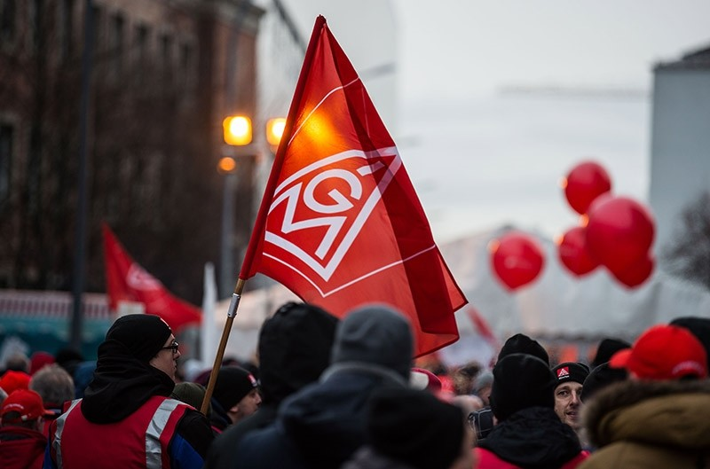 Members of the metalworkers' and electrical industry union IG Metall protest with a flag with the logo of IG Metall during a warning strike in Munich, southern Germany, on February 02, 2018. (AFP Photo)
