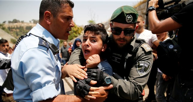 A Palestinian youth is detained by an Israeli border police officer during scuffles that erupted after Palestinians held prayers just outside Jerusalem's Old City