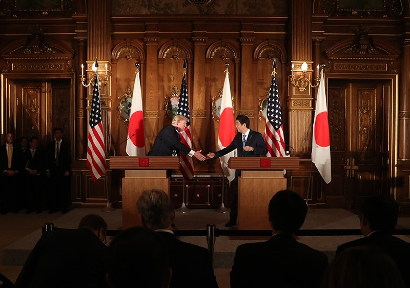 President Donald Trump, left, and Japanese Prime Minister Shinzo Abe, reach out to shake hands each other during a joint news conference at the Akasaka Palace, Monday, Nov. 6, 2017, in Tokyo (AP Photo)
