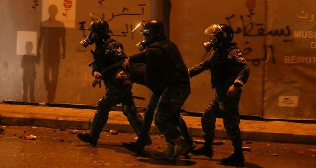 Riot police restrain a protestor during anti-government protests, Beirut, Jan. 18, 2020. REUTERS Photo
