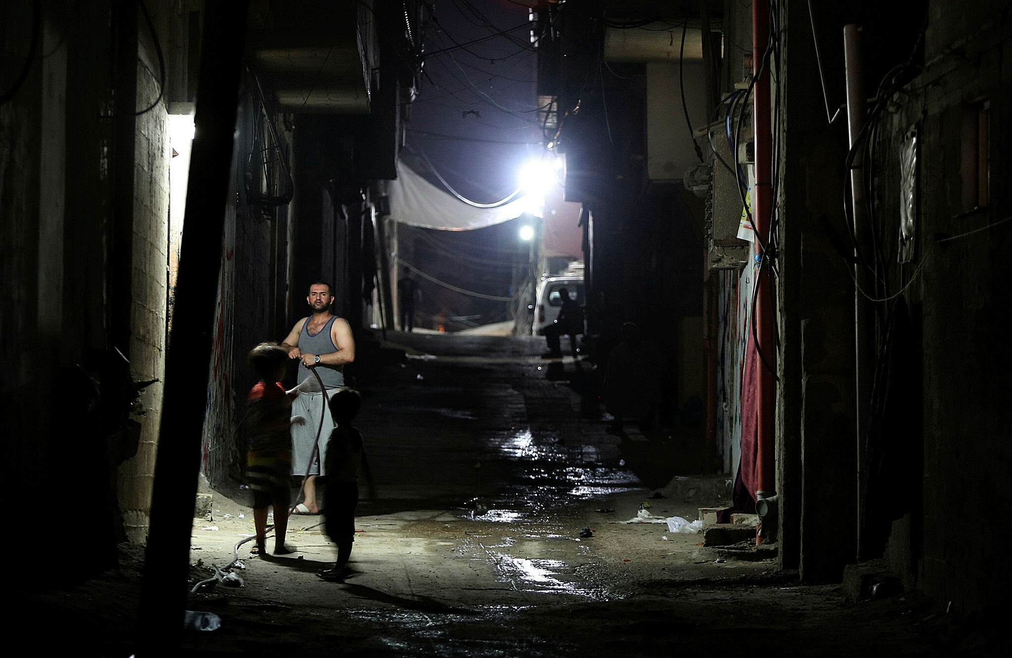 Palestinian refugees seen outside their houses during power outage at Al Shateaa refugee camp in the West Gaza City, 17 July 2017. (EPA Photo)