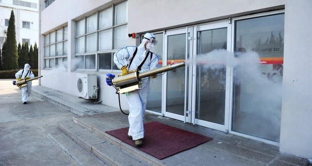 Workers in protective suits spray disinfectant at a business in Qingdao in eastern China's Shandong Province, Feb. 1, 2020. Chinatopix via AP