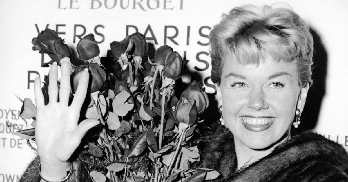 In this April 15, 1955 file photo, American actress and singer Doris Day holds a bouquet of roses at Le Bourget Airport in Paris, France after flying in from London. (AP Photo)