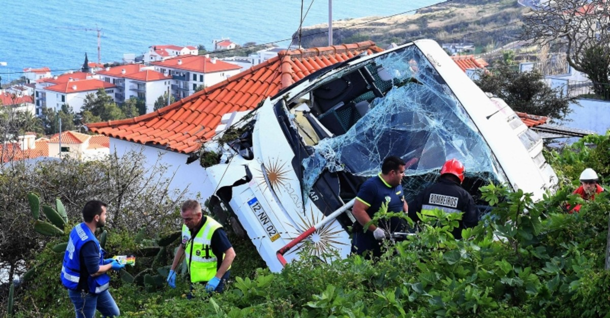 Firemen stand next to the wreckage of a tourist bus that crashed on April 17, 2019 in Caniu00e7o, on the Portuguese island of Madeira. (AFP Photo)
