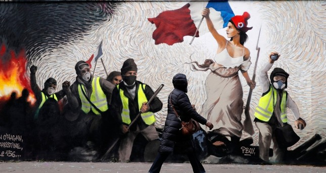 A woman passes by a mural by street artist PBOY depicting Yellow Vest (gilets jaunes) protestors inspired by a painting by Eugene Delacroix, La Liberte guidant le Peuple (Liberty Leading the People), in Paris, Thursday, Jan. 10, 2019. (AP Photo)