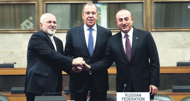 Iranian FM Mohammad Javad Zarif (L), Russian FM Sergei Lavrov (C), and FM Mevlüt Çavuşoğlu (R) shake hands after a joint statement following consultations on Syria, at the European headquarters of the U.N. in Geneva, Switzerland, Dec. 18.