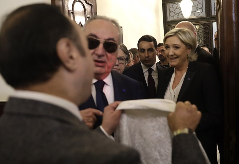An aide of Lebanon's Grand Mufti Sheikh Abdel-Latif Derian, left, gives a head scarf to French far-right presidential candidate Marine Le Pen, right, to wear during her meeting with the Mufti (AP Photo)
