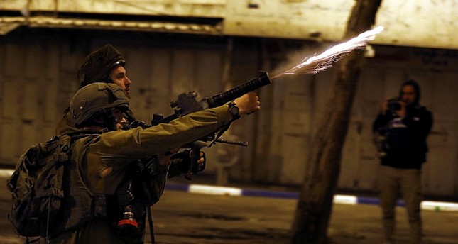Israeli army soldiers shoot tear gas grenades during clashes with Palestinians in the West Bank city of Hebron, May 14, 2018. (EPA Photo)