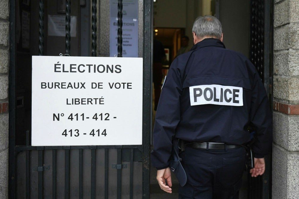 A police officer enters a polling station in Rennes during the first round of the French legislative elections on June 11.