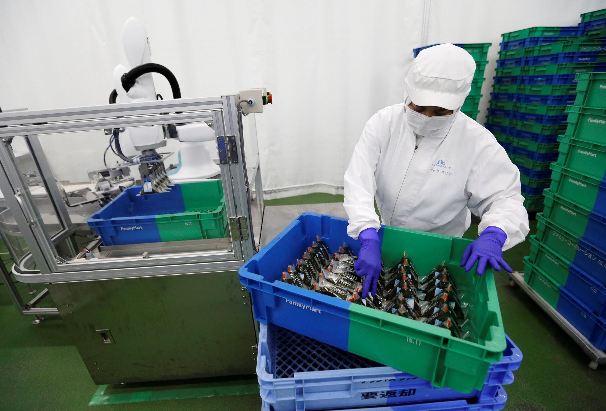 A woman works next a Kawasaki Heavy Industriesu2019 collaborative robot stacking rice balls at Delicious Cook & Cou2019s food factory, Narashino, Japan.