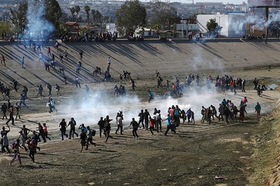 Migrants run from tear gas, thrown by the U.S border patrol, near the border fence between Mexico and the U.S. in Tijuana, Nov. 25, 2018. (Reuters Photo)