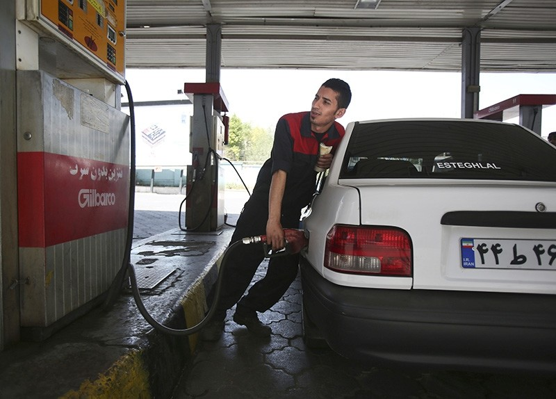 A gas station worker fills a car in central Tehran, Iran, Friday, April 25, 2014. (AP Photo)