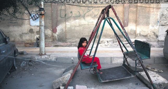 A Syrian girl sits on a swing in eastern Damascus on the first day of the Eid al-Fıtr holiday, which marks the end of the Muslim holy fasting month of Ramadan, July 6, 2016.