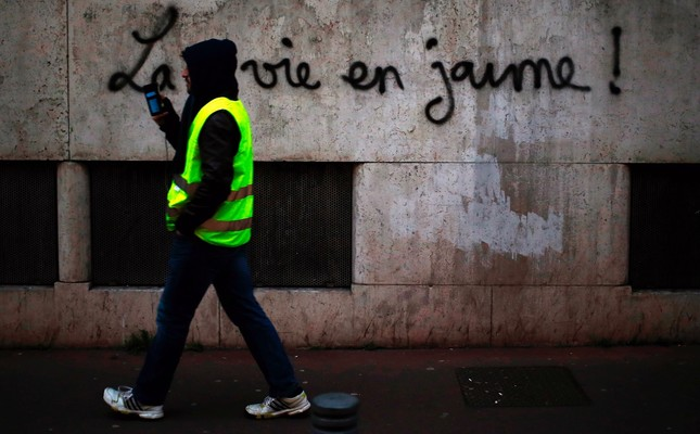 """A man walks along a wall with the inscription """"Life in yellow"""" during a demonstration of """"yellow vest"""" (gilets jaunes) protesters, Rouen, Jan. 5."""