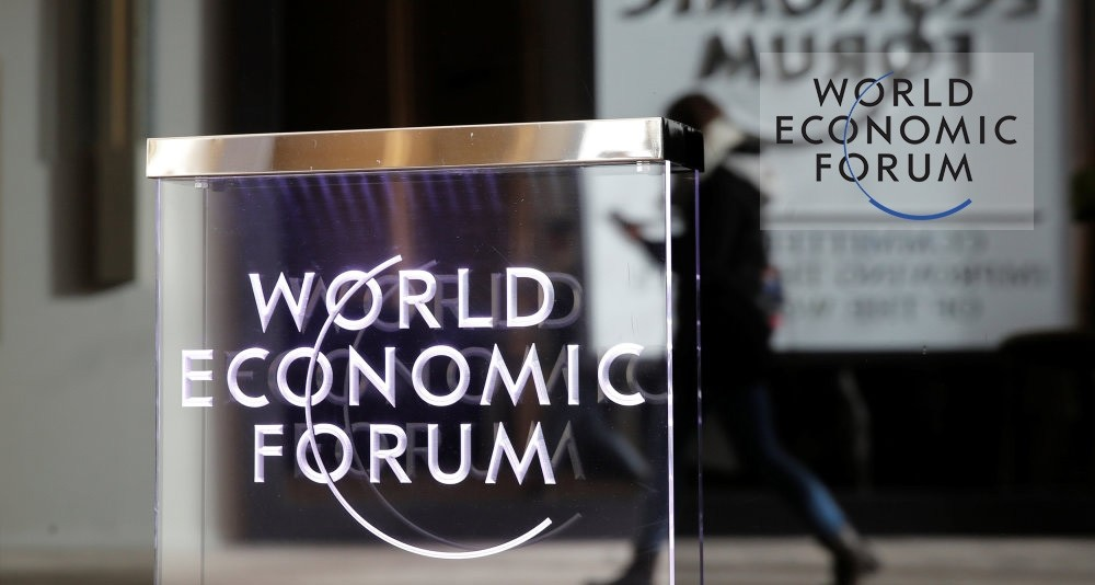 A person passes by a World Economic Forum logo in Davos, Switzerland, Jan. 20, 2019.