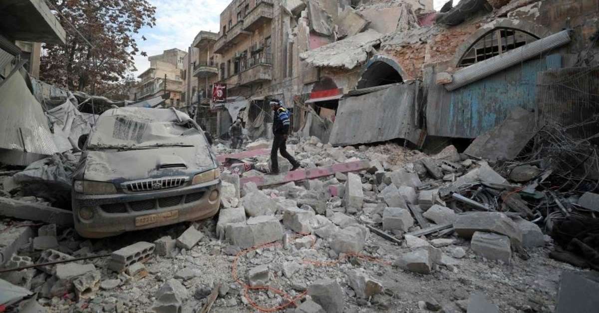 A Syrian man walks on the rubble of a building following a regime airstrike on the town of Ariha in Syria's last major opposition bastion of Idlib, Jan. 15, 2020. (AFP Photo)