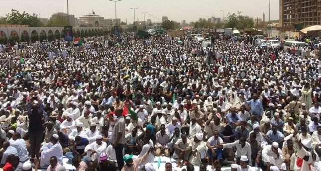 Sudanese protesters gather near the military headquarters in Khartoum as they continue to rally demanding a civilian body to lead the transition to democracy one day after a military council took control of the country, on April 12, 2019. (AFP Photo)