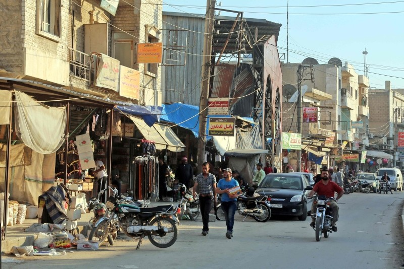 A picture taken on June 6, 2018, shows people walking in a street in the northern Syrian town of Manbij. (AFP Photo)