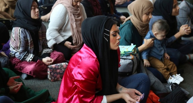 In this Dec. 27, 2019, photo, Amani Al-Khatahtbeh, center, sits near the back of the room at the Islamic Center of New York University during Friday prayers. AP Photo