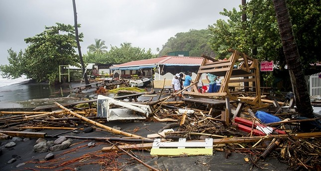 People stand next to debris at a restaurant in Le Carbet, on the French Caribbean island of Martinique, after it was hit by Hurricane Maria, on September 19, 2017. (AFP Photo)