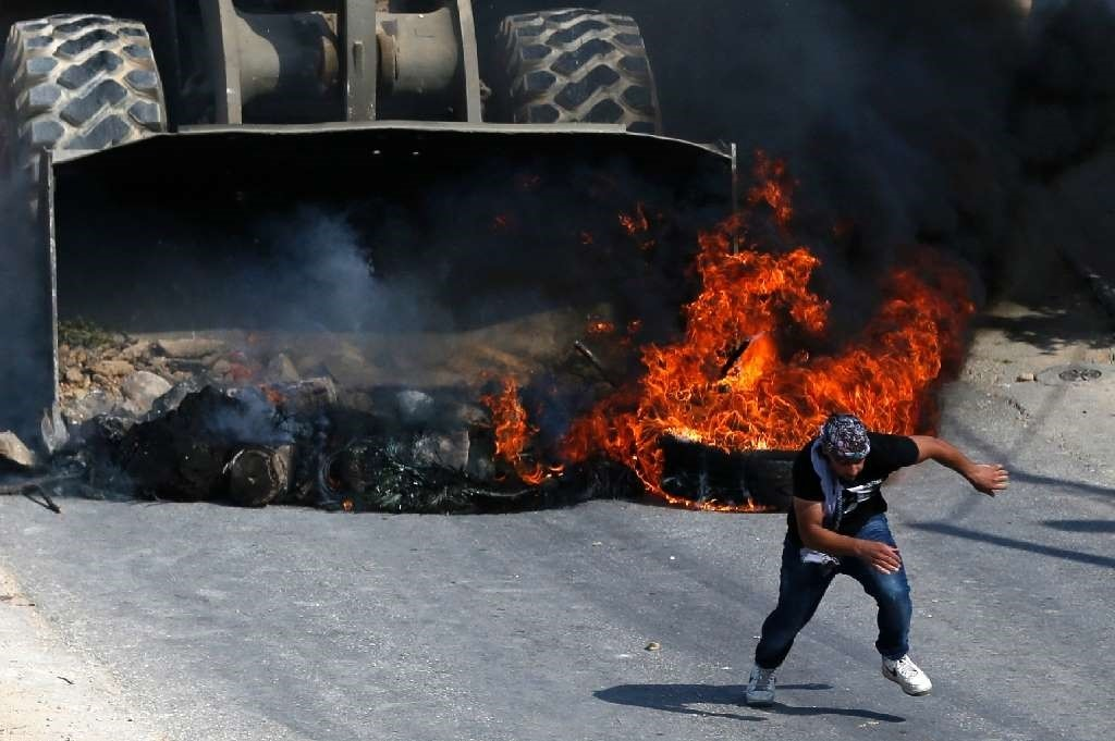 A Palestinian runs from the path of an Israeli army bulldozer during clashes in the village of Kobar, west of Ramallah, on July 22.