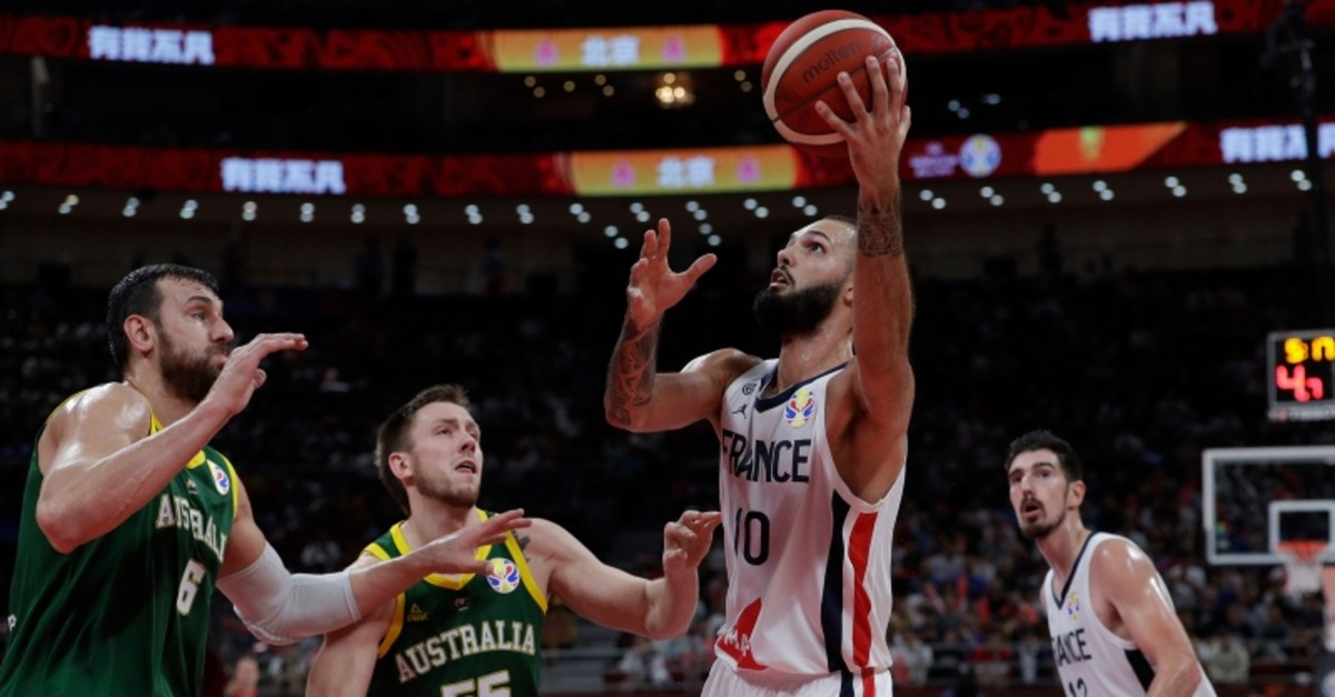 Evan Fournier of France goes for a shot over Andrew Bogut, left, and Mitch Creek of Australia during their third placing match for the FIBA Basketball World Cup at the Cadillac Arena in Beijing, Saturday, Sept. 13, 2019. (AP Photo)