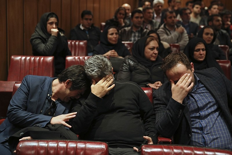 Friends and colleagues of the deceased Iranian seafarers aboard a tanker that sank off the coast of China weep at the headquarters of National Iranian Tanker Company, in Tehran, Iran, Sunday, Jan. 14, 2018. (AP Photo)