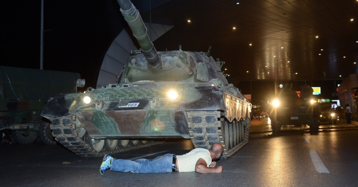 Metin Dou011fan, one of the civilians who went to the airport to confront the putschists, lies down in front of a tank commanded by the putschists at the airport, July 15, 2016.