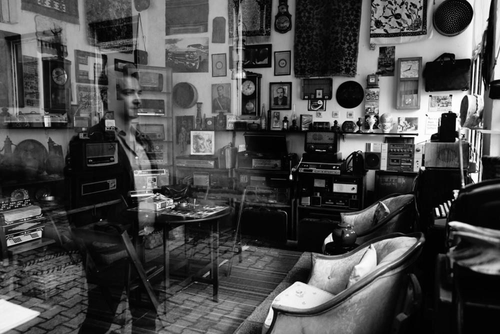 A man looks in through the window of an antique shop.