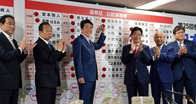 Japanese PM and ruling Liberal Democratic Party (LDP) president Shinzo Abe (3rd L) celebrates as he attaches paper flowers on the winning candidates of the Parliament's upper house election at the party's headquarters in Tokyo on July 21, 2019. (AFP)