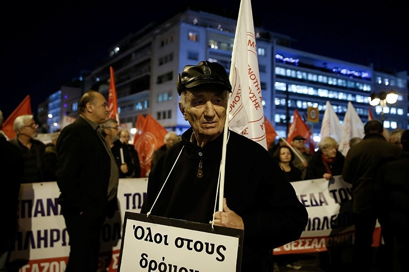 A pensioner takes part in a demonstration against planned pension reforms outside the parliament building in Athens, Greece, December 15, 2017. (Reuters Photo)
